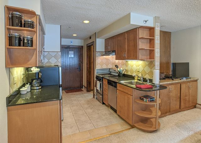 Kitchen with coffee pot, fridge, oven, stove, and dishwasher.