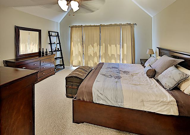 Master bedroom with King bed and adjoining bathroom and ceiling fan