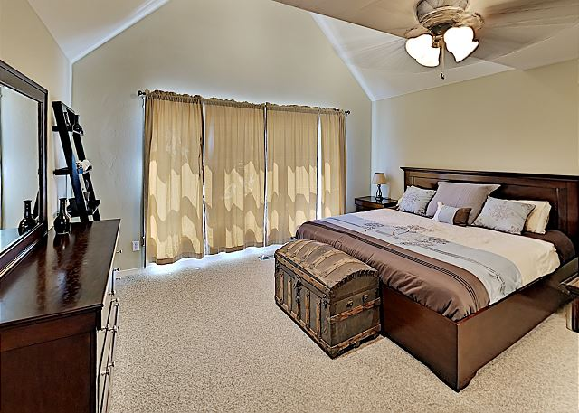 Master bedroom with King bed and adjoining master bathroom and ceiling fan.