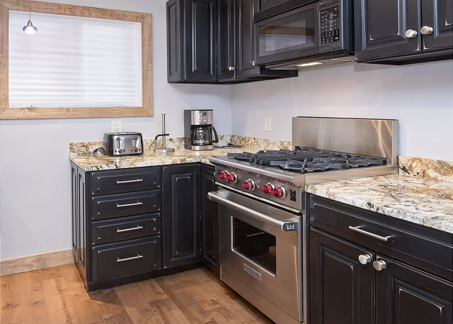 Nice granite countertops with a high end stove.