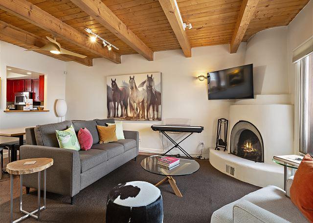 Living area with kiva fireplace, piano, smart TV and a sleeper sofa