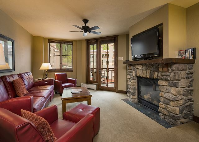 Durango, CO vacation rental at Purgatory Resort. Living room with fireplace, tv, and access to balcony with plaza views. Ski-in/Ski-out condo in Purgatory Lodge.