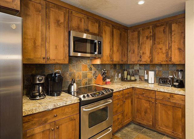 Kitchen and bar area. Fully stocked with cookware and dishware. Traditional drip coffee maker.