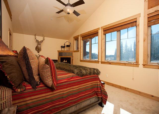 Bedroom with king size bed, fireplace, and ceiling fan