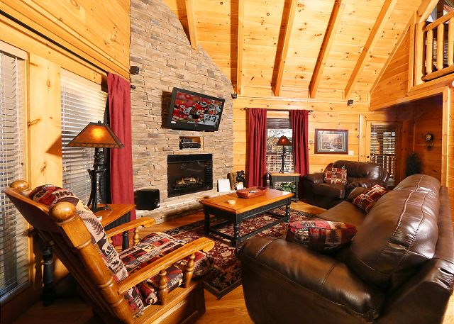 The main room of the cabin with fireplace and flat screen TV.