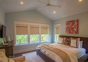 King Suite with flat screen TV, ceiling fan, luxury linens, and en suite bath