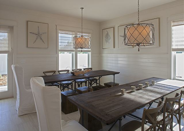 Dine under stately light fixtures with side by side dining tables.