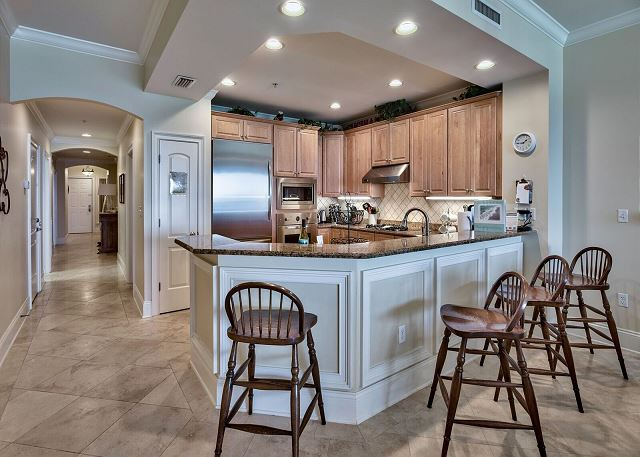 Kitchen with bar stools around granite counter top