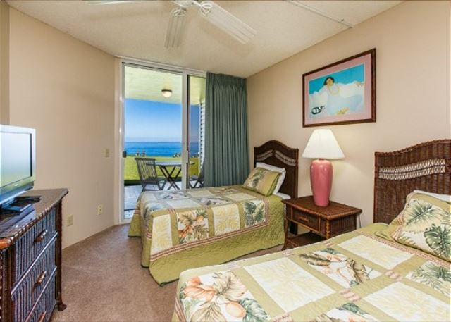 Ground floor bedroom with two twin beds and outdoor lanai facing the ocean.