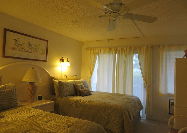 Bedroom with 2 queen beds, TV, ceiling fan and air conditioner.