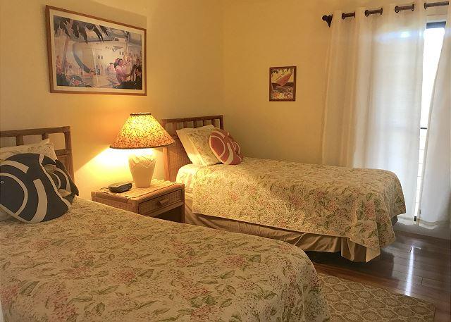 Twin beds in first level bedroom with en-suite bathroom