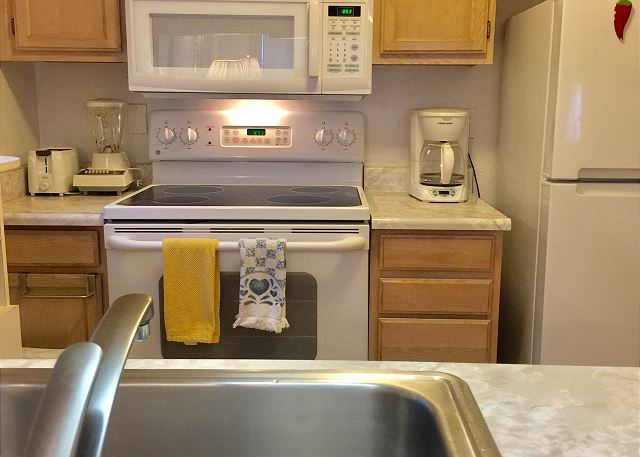 Kitchen with full size stove, refrigerator, blender, coffee make