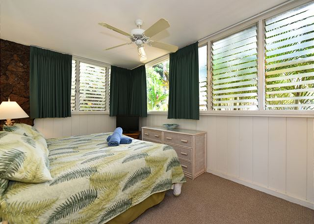 Breezy bedroom surrounded by tropical plants. Lava rock wall accent