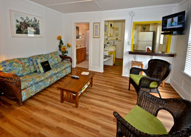 A Spacious Living Room Area With a Flat Screen TV and Comfortable Tropical Furnishings.
