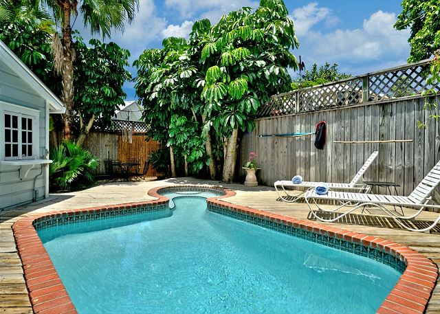 Private Free Form Pool and Deck Area With Lush Plantings, Loungers, and Decking