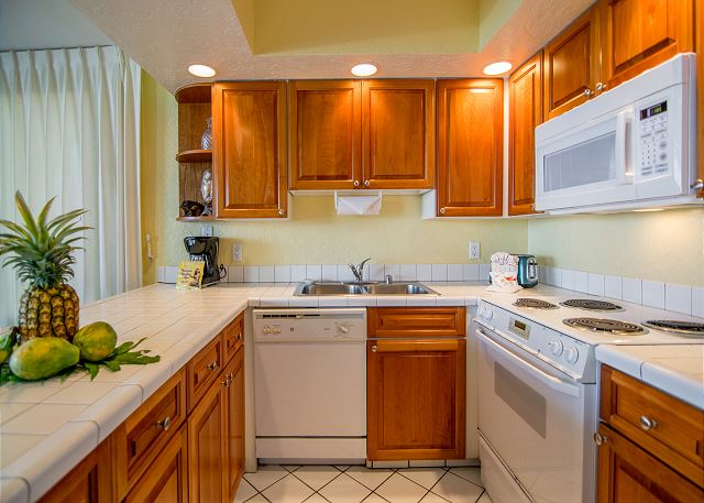 Beautiful wood cabinets with all white appliances and counter tops.