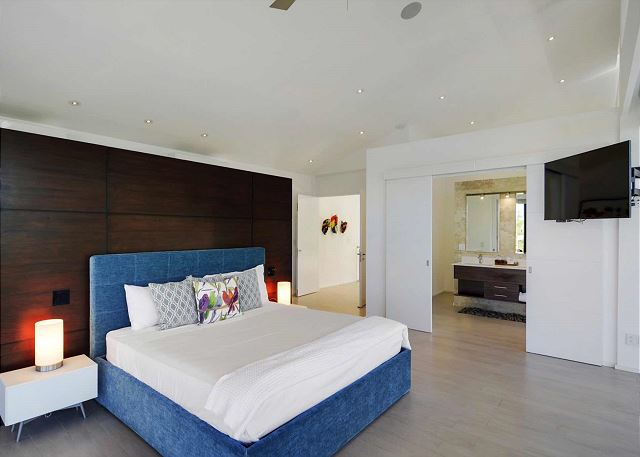 King bed, flat screen TV, closet, and full bath in Master Suite
