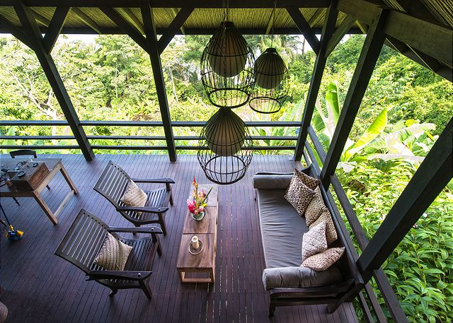 A second floor terrace overlooks the living area and jungle foli
