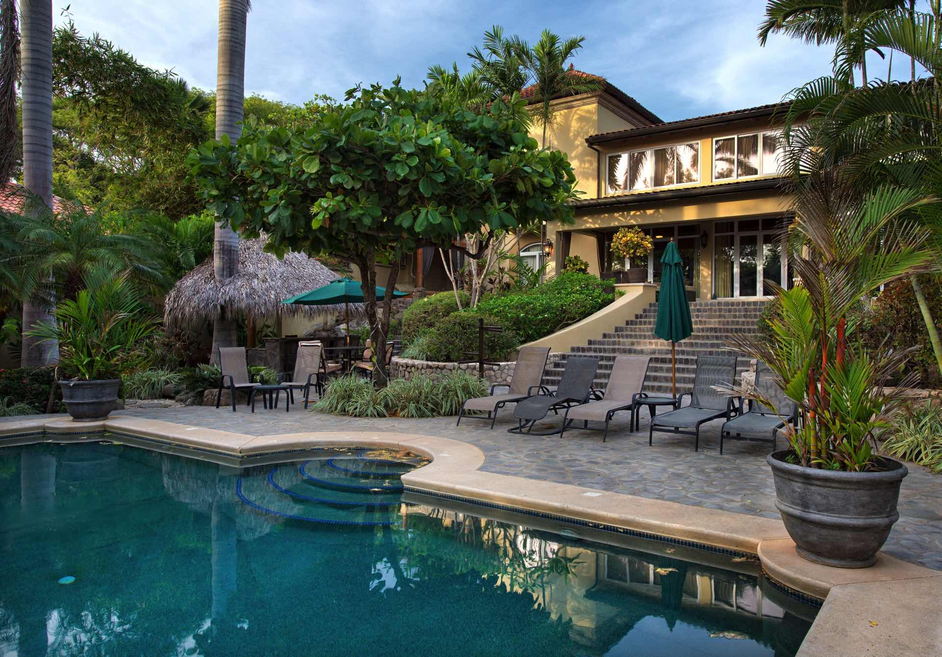 Beach house with hotel-size pool, palapa bar, and grand stairca