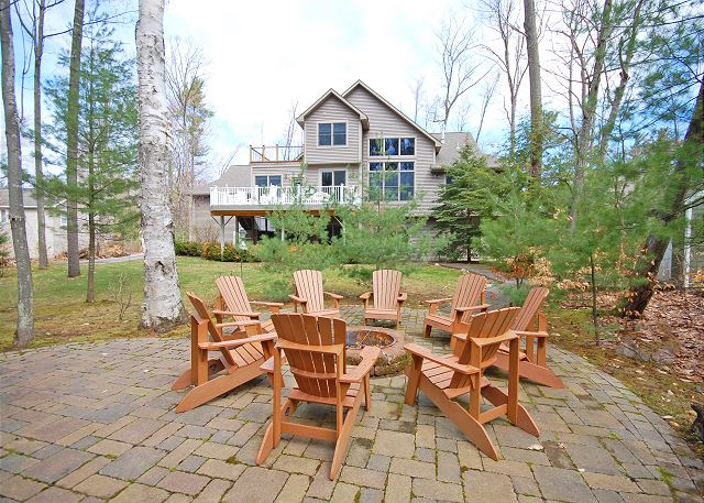 The beautiful back yard with multiple Adirondack chairs and fire pit!