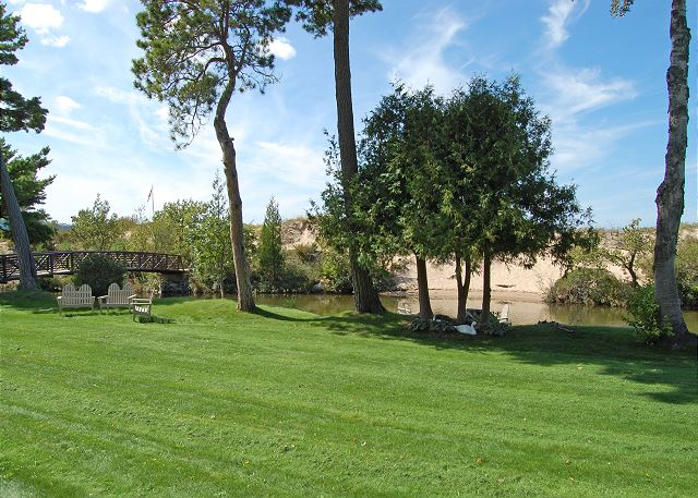 View of lawn and riverfront area in front of condo. The footbridge to the beach is directly to the left in this photo!