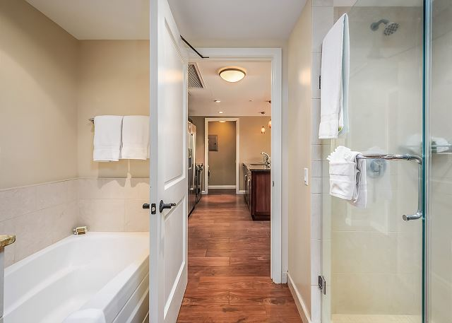 The bathroom has a bathtub and a stand up shower