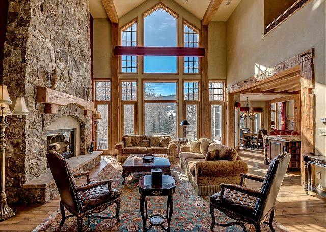 Elegant Beaver Creek Chateau Great Room With Two Story Vaulted Ceilings, Floor To Ceiling Windows With Views Towards Beaver Creek, And A Floor To Ceiling Gas Fireplace