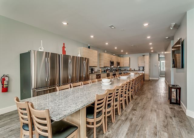 """Long granite table with seating for 22, 2 of each appliance, 3 refrigerators, large 75"""" flat screen tv"""