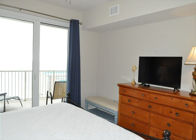 Master bedroom with balcony access and flat screen TV