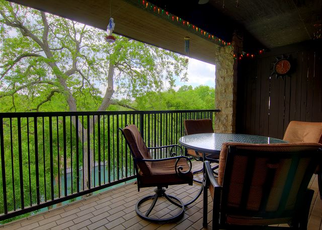 The covered balcony offers views of the river, great for sipping coffee in the morning or watching tubers float by during an outdoor dinner.