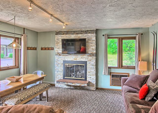 Spacious Living Room with Fireplace, Flat Screen Television, Sofa Sleeper, and lots of Natural Light in this Wide Open Floor Plan.