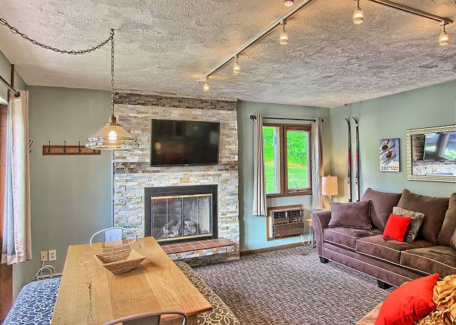 Another View of the Spacious Living Room with Fireplace, Flat Screen Television, and lots of Natural Light in this Wide Open Floor Plan.