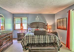 Spacious Master Bedroom with King Bed, Flat Screen TV, Lot of Natural Light, and En Suite Bathroom.