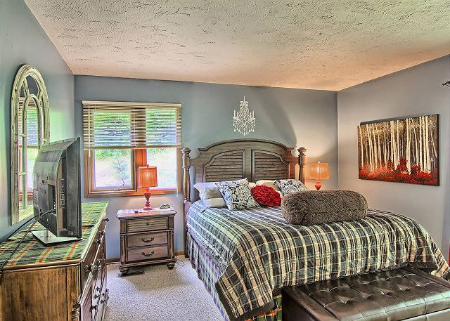 Another View of the Spacious Master Bedroom with King Bed, Flat Screen TV, Lot of Natural Light, and En Suite Bathroom.