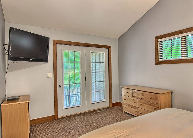 Spacious Master Bedroom with King Bed, Flat Screen TV, DVD Player, Private Entrance from Deck, and En Suite Bathroom.