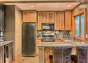 Fully Equipped Gourmet Kitchen with Breakfast Bar, Built In Wine Cooler, and Granite Counter Tops.