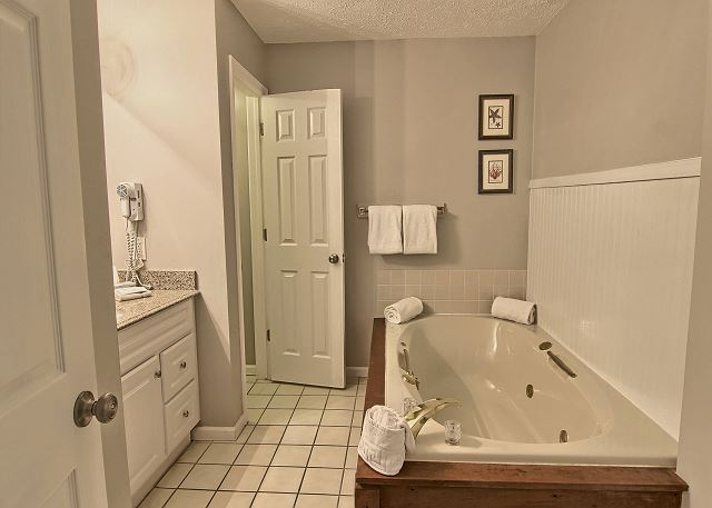 This huge bathroom includes a jetted jacuzzi tub, shower, vanity with lots of space and a separate area for the toilet.