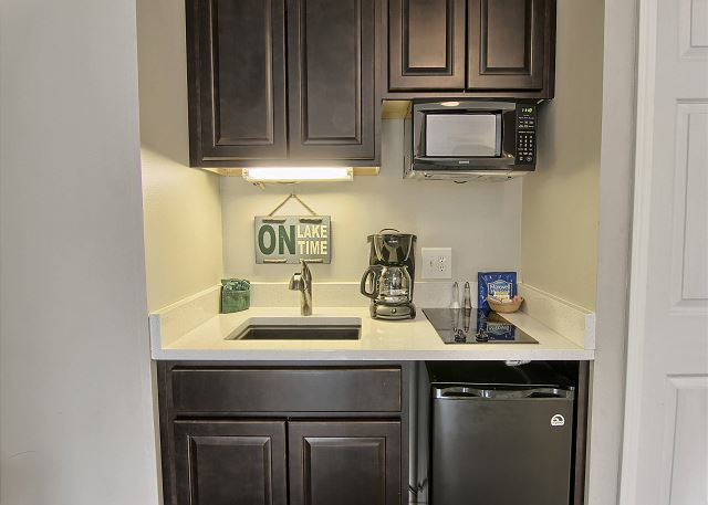 This lovely kitchenette area has everything you may need on vacation. It includes a stove-top, microwave, small fridge, coffee maker, sink, toaster & dishwasher. Plus a table with two chairs.