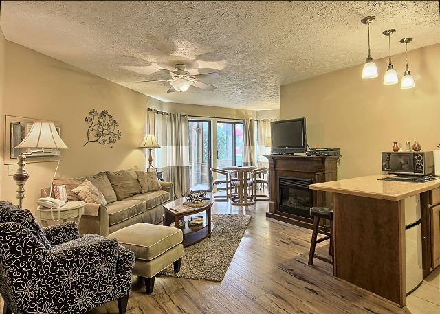 This spacious living room includes a sleeper sofa couch, a chair with a detachable foot rest, TV with DVD player, Electric fireplace and a round dining table with four chairs.
