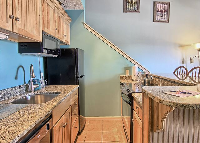 There are granite counter tops in the kitchen, one housing the stainless steel sink and the table with seating for three. There is full stove, microwave, coffee maker, toaster, dishwasher and an average sized refrigerator