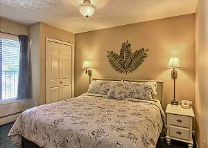 This bedroom has a comfortable king sized bed, two bedside tables, a dresser, closet and TV with cable