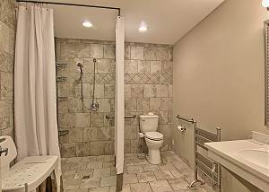 This bathroom is handicap accessible with a spacious open shower, toilet with a bidet, wheelchair accessible sink, heated towel rack, and shower seat if need.
