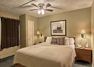 The bedroom in this unit has a comfortable king sized bed, two bedside tables, a dresser, closet and TV with cable.