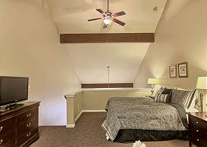 This bedroom, which is located in the loft space has a king size bed, bed side tables with lamps, dresser and a tv.