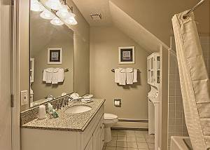 This bathroom which is located next to the bedroom has a full size vanity and a shower/bathtub.