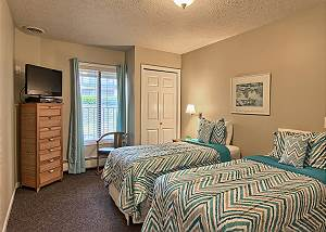 This unique unit has twin beds in one of the bedroom areas. This bedroom also has bedside tables with lamps, dresser and tv.