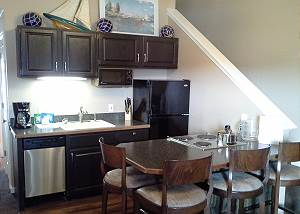 This kitchen includes full size fridge, microwave, coffee maker, dishwasher, toaster, small stove and lots of counter space which also includes four barstools for eating.