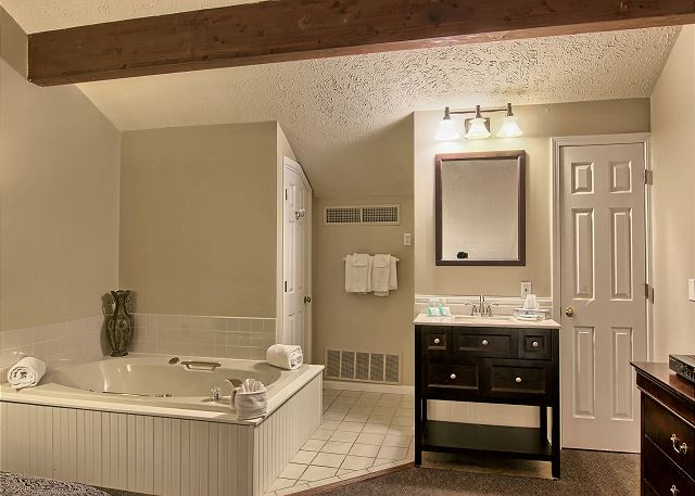 The second bathroom which is located also in the loft area has a jet jacuzzi tub, vanity, shower and a inclosed toilet area.