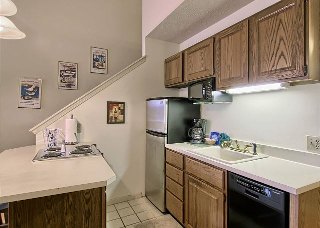 This kitchen has a full-sized fridge, stove, microwave, dishwasher, toaster and coffee maker