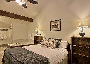 The bedroom in this unit has a comfortable king sized bed, two bedside tables, a dresser, closet and TV with cable